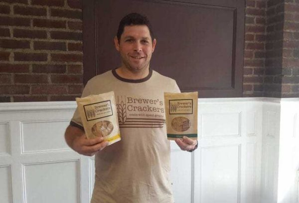 Brewer's Crackers co-owner holding 2 bags of crackers